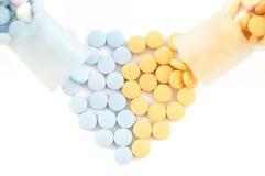 Píldoras y drogas que forman el corazón en blanco Imagen de archivo libre de regalías