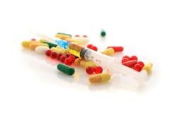 Píldoras y jeringuilla. Imagen de archivo libre de regalías