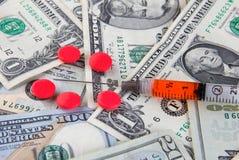 Píldoras y jeringuilla en billetes de dólar Fotos de archivo