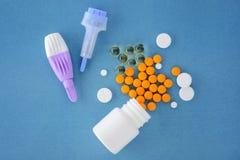 píldoras y lancetas adulto y niños en un fondo azul Fotografía de archivo