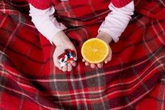 Píldoras y naranja en manos Fotos de archivo