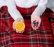 Píldoras y naranja en manos Imagen de archivo