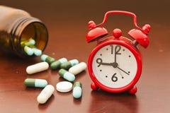Píldoras y reloj Imagenes de archivo