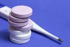 Píldoras y termómetro Imagenes de archivo