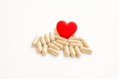 Píldoras y un corazón imágenes de archivo libres de regalías