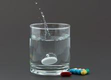 Píldoras y vidrio de agua en fondo gris Fotos de archivo libres de regalías