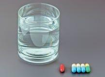 Píldoras y vidrio de agua en fondo gris Imagen de archivo libre de regalías