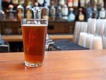Pół kwartego szkło piwny obsiadanie na barze odpierającym w dnia czasie obrazy royalty free