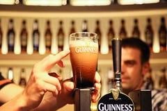 Pół kwarty Guinness z palcowy wskazywać Fotografia Royalty Free