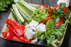 Półmisek asortowani świezi warzywa i feta ser na lekkim drewnianym tle zdjęcia royalty free