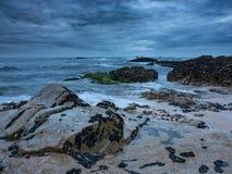 Półmrok na skalistej plaży z dramatycznymi chmurami i ciemnym markotnym niebem d?ugo ekspozycji zdjęcie stock
