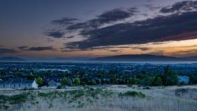 Półmrok spada nad śpiącym miastem w dolinie z górami i jeziorem w tle zdjęcia stock