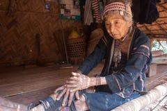 Północ Tajlandia podczas gorącego lata Stara kobieta od Akha grupy etnicza, odpoczynków w cieniu jej domu robić drewno i półdupkó Zdjęcie Stock