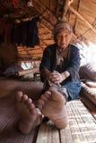 Północ Tajlandia podczas gorącego lata Stara kobieta od Akha grupy etnicza, odpoczynków w cieniu jej domu robić drewno i półdupkó Obraz Royalty Free