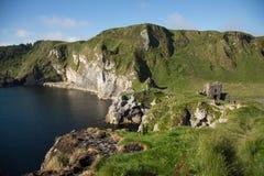 Północna Irlandia, Kinbane kastowa ruina, zielona trawiasta obwódka, błękitny morze i ocean, krajobraz Zdjęcie Stock