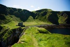 Północna Irlandia, Kinbane kastowa ruina, zielona trawiasta obwódka, błękitny morze i ocean, krajobraz Fotografia Royalty Free