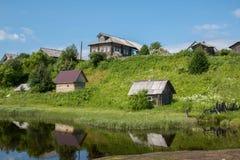 Północna Rosyjska wioska Isady Letni dzień, Emca rzeka, stare chałupy na brzeg, stary drewniany most i chmur odbicia, Obraz Stock
