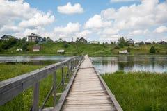 Północna Rosyjska wioska Isady Letni dzień, Emca rzeka, stare chałupy na brzeg, stary drewniany most i chmur odbicia, Zdjęcia Royalty Free