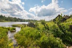 Północna Rosyjska wioska Isady Letni dzień, Emca rzeka, stare chałupy na brzeg, stary drewniany most i chmur odbicia, Fotografia Stock