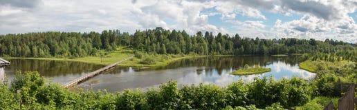 Północna Rosyjska wioska Isady Letni dzień, Emca rzeka, stare chałupy na brzeg, stary drewniany most i chmur odbicia, Obrazy Stock