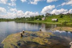 Północna Rosyjska wioska Isady Letni dzień, Emca rzeka, stare chałupy na brzeg, stary drewniany most i chmur odbicia, Fotografia Royalty Free