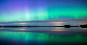Północni światła tanczy nad spokojnymi jeziornymi zorz borealis Fotografia Royalty Free