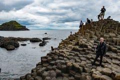 PÓŁNOCNI, 2017: okręg administracyjny ANTRIM Irlandia, SIERPIEŃ 27 - Grupa turyści bada Gigantycznego ` s droga na grobli Zdjęcie Stock