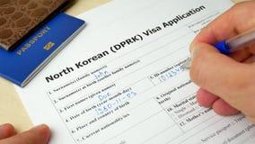 Północno-koreański DPRK wniosku wizowego forma z paszportem i piórem zdjęcie wideo