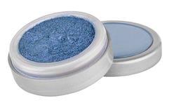 Pó azul da sombra da cor com partículas do brilho, no recipiente aberto cinzento redondo que senta-se em sua tampa, produto de be imagem de stock royalty free