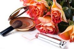 Pó, batom e rosas sobre o branco Fotografia de Stock Royalty Free