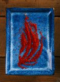 Pó da especiaria do açafrão na placa azul fotografia de stock royalty free