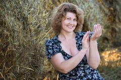 Pó da mulher oneself no campo em um fundo de pacotes da palha Fotos de Stock Royalty Free