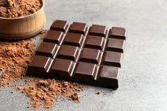 Pó de barra e de cacau de chocolate no cinza imagens de stock royalty free