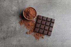 Pó de barra e de cacau de chocolate no fundo cinzento imagem de stock