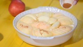 Pó de espalhamento da canela na torta de maçã Mão que polvilha o condimento no bolo de maçã Fazendo a torta de maçã doce Maçã cas filme