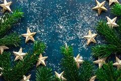 Pó dourado decorativo macio fresco da neve dos ornamento da estrela dos ramos de árvore do abeto em escuro - contexto azul de tur fotografia de stock royalty free