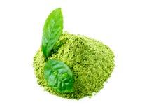 Pó verde do chá do matcha com as folhas molhadas verdes isoladas no branco foto de stock