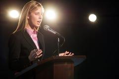 Pódio de Giving Speech At da mulher de negócios no auditório