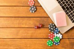 Póker en línea Ordenador portátil, fichas de póker, dados, una cubierta de tarjetas en un wo foto de archivo libre de regalías