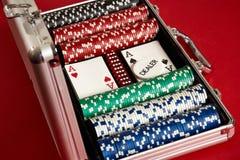 Póker fijado en maleta del metal Entretenimiento aventurado del juego Opinión superior sobre fondo rojo fotografía de archivo