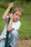 Pólo de escalada do rapaz pequeno no campo de jogos Fotografia de Stock