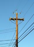 Pólo de potência de madeira do pólo de telefone de encontro ao céu azul Imagens de Stock
