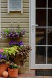 Pórtico maravillosamente adornado de una casa privada, flores coloridas en los potes de arcilla grandes, banco del vintage, inven Imagen de archivo libre de regalías