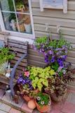 Pórtico maravillosamente adornado de una casa privada, flores coloridas en los potes de arcilla grandes, banco del vintage, inven Fotos de archivo