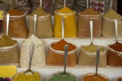 Pós coloridos brilhantes e especiarias secadas nos sacos com as colheres no contador fotografia de stock
