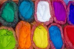 Pós coloridos muito brilhantes de uma pintura nos sacos e em uma colher pequena pinturas para o feriado de Holi foto de stock