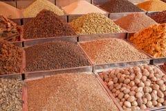 Pós e sementes coloridos diferentes indianos da especiaria em bandejas quadradas do metal no contador imagens de stock