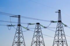 Pôles de ligne électrique au-dessus de fond de ciel bleu Image libre de droits