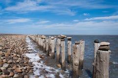 Pôles près d'océan avec des pierres ont mis en fonction le dessus Photo stock