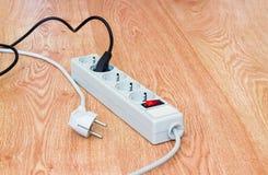 Põe a barra e as duas tomadas de poder com cabos dos canos principais no surfac de madeira Imagem de Stock